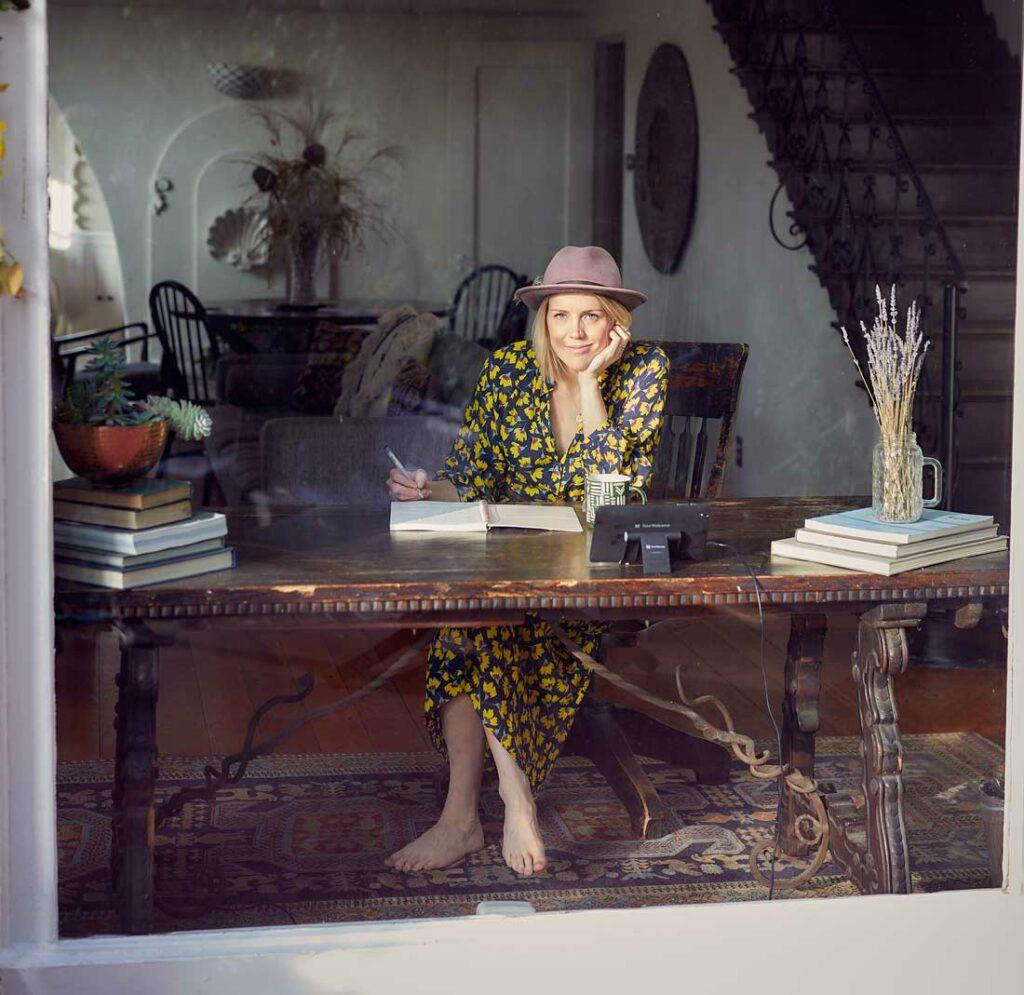 pisząca kobieta w sukience i niewielkim kapeluszu, patrząca przez szybę wewnątrz staromodnego, eleganckiego budynku