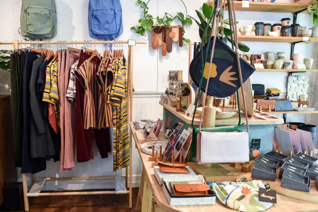 warsztat projektanta mody, drewniane stojaki, na ktorych znajdują się ubrania, artystyczna przestrzeń twórcza