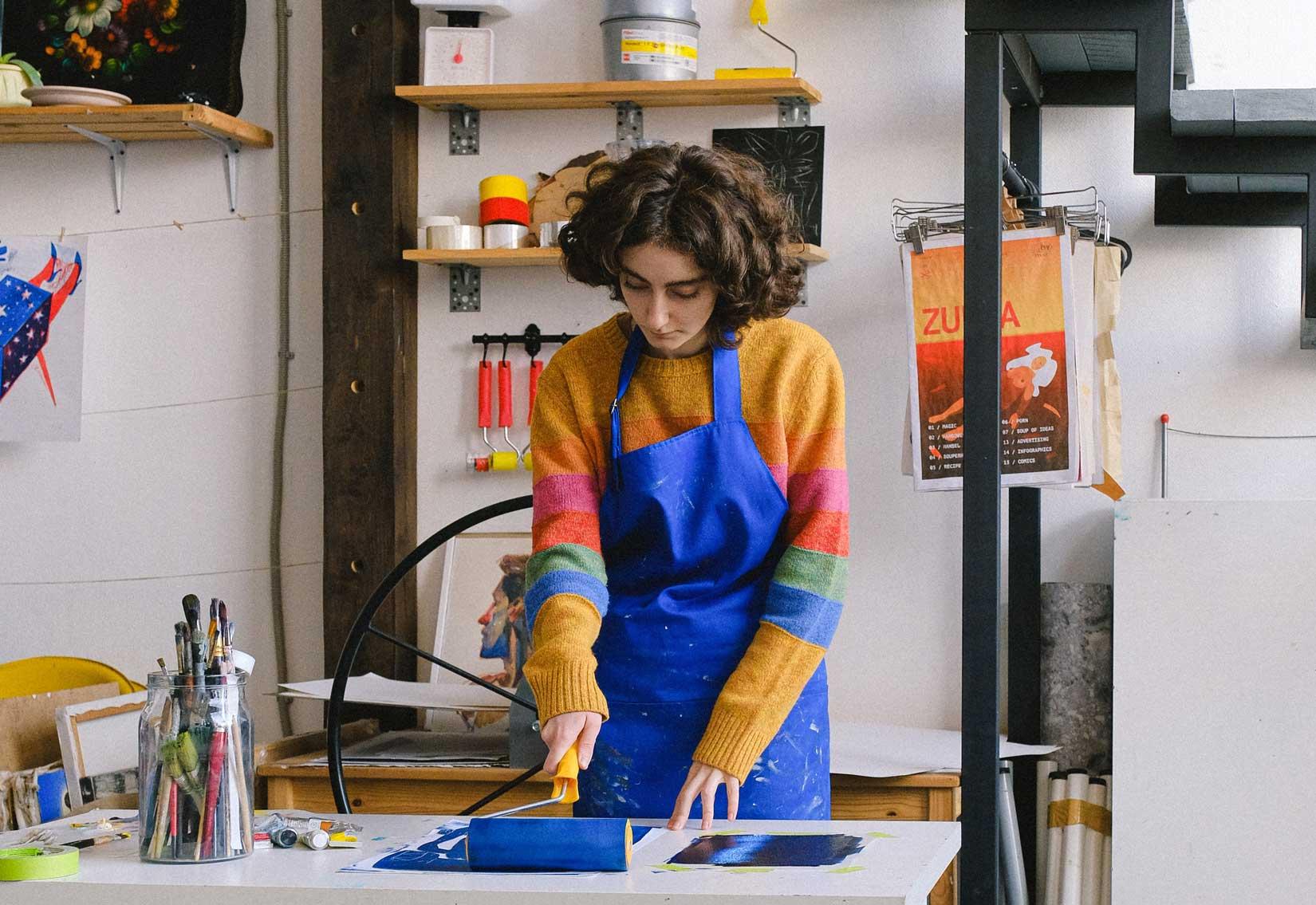 kobieta w kolorowym swetrze i niebieskim fartuchu, uprawiająca zawody artystyczne